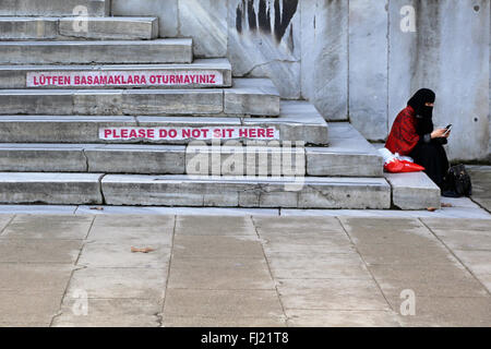 A Muslim woman sits on the steps of Blue mosque with 'please do not sit here' sign , Istanbul - Stock Photo