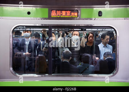 Crowd  and rush hour in the early morning for employees in the metro of Tokyo , Japan - Stock Photo