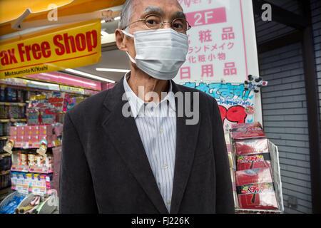 Japanese man wearing surgical mask in Tokyo - Stock Photo