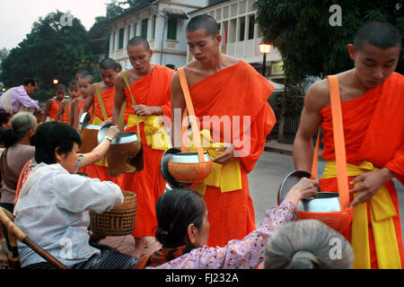 Tak bat ritual - Buddhist monks receive rice and  food from pupulation in early morning in Luang Prabang , Laos, - Stock Photo