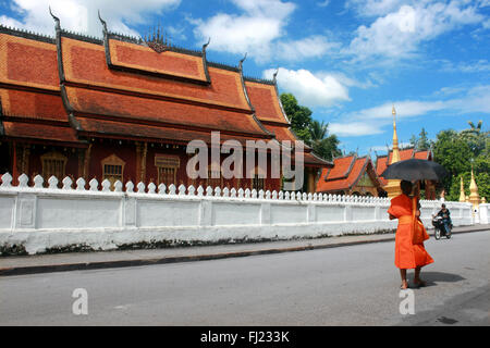 Buddhist monk walking in the streets of Luang Prabang in front of Wat Mai temple , Laos, Asia - Stock Photo