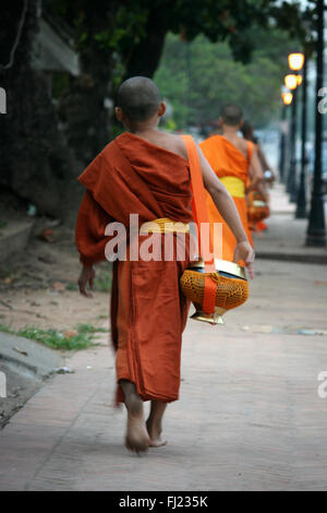 Buddhist monk walking in the streets of in Luang Prabang , Laos, Asia - Stock Photo