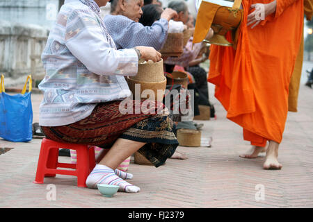 Tak bat ceremony in the morning - Buddhist monks receive rice and food from population in  in Luang Prabang , Laos, - Stock Photo