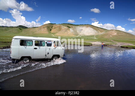 Old Russian van travelling in Mongolia through a river in the middle of nowhere - Stock Photo