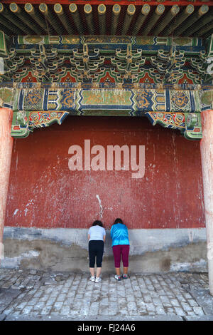 Two women praying inside the Inside the Erdene Zuu monastery , Mongolia - Stock Photo