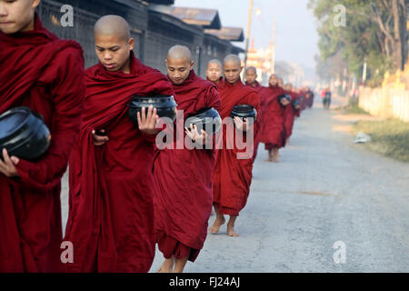 Buddhist monks receive rice from population, daily ritual, Nyaung-U, Myanmar - Stock Photo