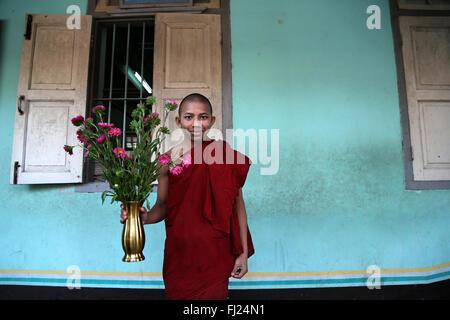 Young buddhist monk with flowers in monastery in Amarapura, Myanmar - Stock Photo