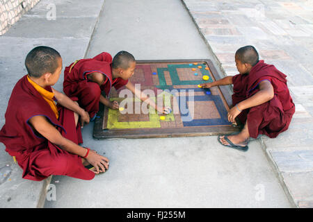 Buddhist monks playing in monastery, gompa, in Boudhanath, Nepal - Stock Photo