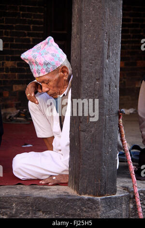 Nepalese Newar man with traditional costume and hat  'Dhaka topi' , in a temple in Patan, Nepal - Stock Photo