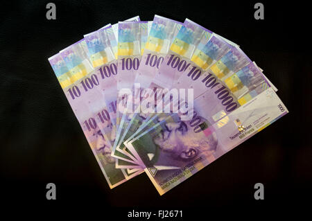 Swiss 1000 francs banknotes shown as a fan on black background. The purple notes feature a portrait of Jacob Burckhardt. - Stock Photo