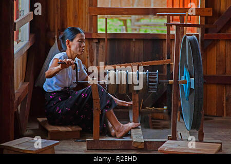 The weaving of LOTUS SILK fabric from the stalks of the lotus plant is a local industry of INLE LAKE - MYANMAR - Stock Photo