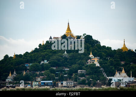 MANDALAY, Myanmar - The gold covered umbrella of on the many temples in the hills of Sagaing, near Mandalay, as - Stock Photo