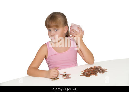 Girl with piggy bank and euro coins on the table isolated - Stock Photo