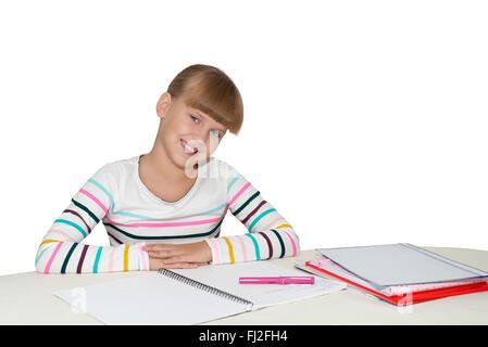 Little cute girl doing homework at the desk isolated - Stock Photo