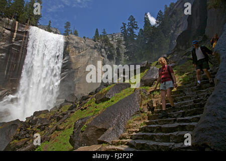 Hikers below VERNAL FALLS which drops 317 during the SPRING run off - YOSEMITE NATIONAL PARK, CALIFORNIA - Stock Photo