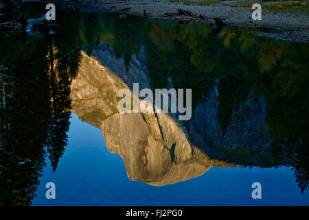 HALF DOME is reflected in the MERCED RIVER during  the fall season - YOSEMITE NATIONAL PARK, CALIFORNIA - Stock Photo