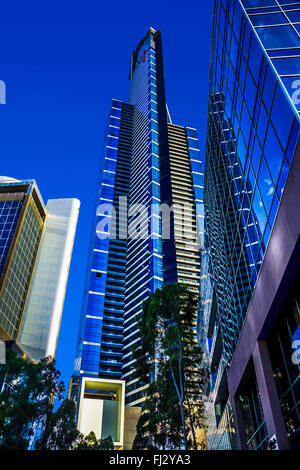 Eureka Tower and other magnificent glass skyscrapers tower above in vivid blue, the Southbank precinct of Melbourne - Stock Photo