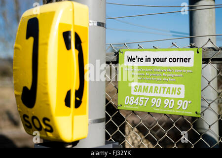 Suicide prevention through Samaritans sign and telephone at unmanned level crossing - Stock Photo