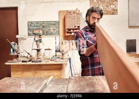 Carpenter expertly checking a wooden plank for straightness and - Stock Photo