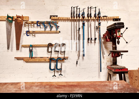 Workshop wall with tools in rows alongside a drill press - Stock Photo