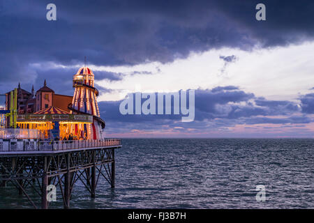 A view from shore of the sea and the amusements on the end of Brighton's Palace Pier taken at dusk