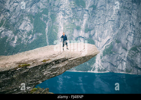 Young man standing on rock in the mountains of Norway. Natural attractions of Trolltunga - Troll tongue. - Stock Photo