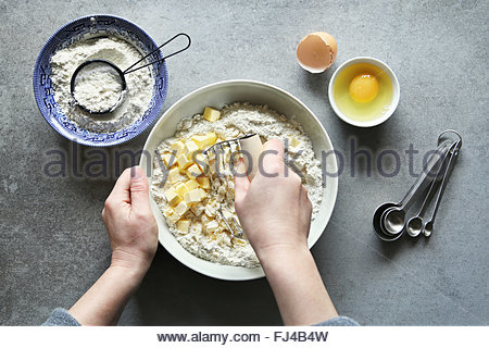 Preparing pastry crust.Female hands cutting butter into the flour with pastry blender.Top view - Stock Photo