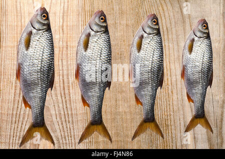 Some raw fish lying on a wooden background. - Stock Photo