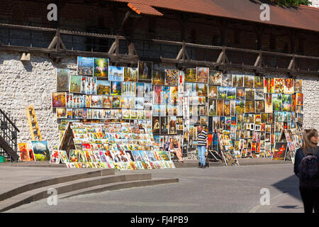 Wall of paintings for sale by local artists outside St. Florian's Gate on Pijarska street in Krakow, Poland - Stock Photo