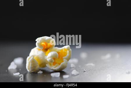 Single popcorn and salt isolated on black background - Stock Photo