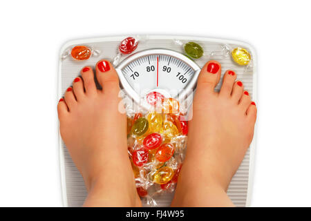 Photo of bathroom scale with candy - Stock Photo