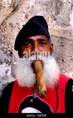 older Cuban with full beard and beret smoking a long cigar, portrait, Cuba, La Habana - Stock Photo
