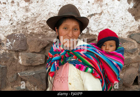 woman in traditional clothing carrying piggyback her baby in a sling, portrait, Peru, Pisaq - Stock Photo