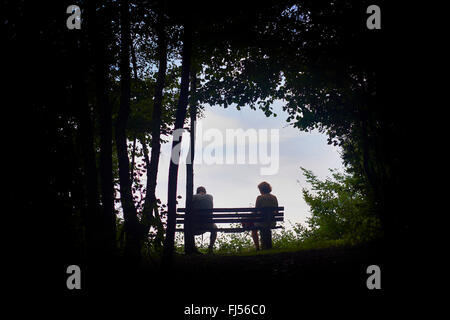 man and woman sitting on a bench at the end of a long and arduous journey, Volme Hoehenring, Germany, North Rhine - Stock Photo