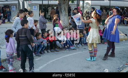 LESVOS, GREECE - October 15, 2015: Clowns arrange representation for refugees to support them. - Stock Photo
