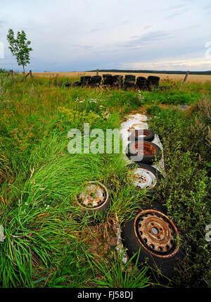 plastic sheet and old tires on silo in field landscape , Germany, Hesse - Stock Photo