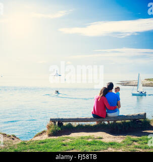 Family with Little Baby on a Bench near Sea - Stock Photo
