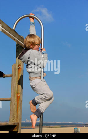 little boy on a climbing frame by the sea, portrait of a child - Stock Photo