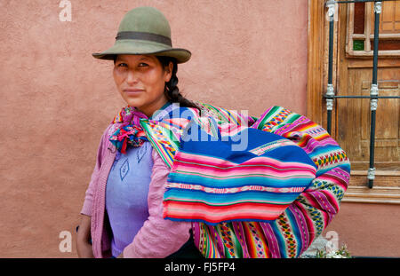 woman in traditional clothing carrying piggyback her baby in a sling, portrait, Peru, Pisaq