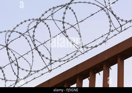 concertina wire, barbed wire on a rusty fence, Germany, Wuppertal - Stock Photo