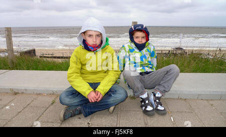 two cool boys sitting together at the North Sea Coast, Netherlands - Stock Photo