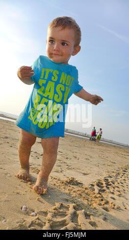 little boy wearing a T-shirt on a sandy beach, Netherlands - Stock Photo