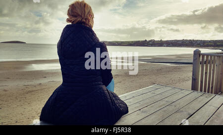 young elegant woman sitting on wood on beach - Stock Photo
