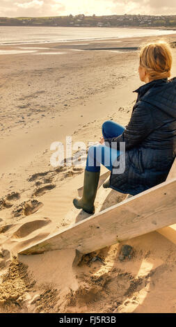 young blond female sitting on cabin stairs on beach - Stock Photo