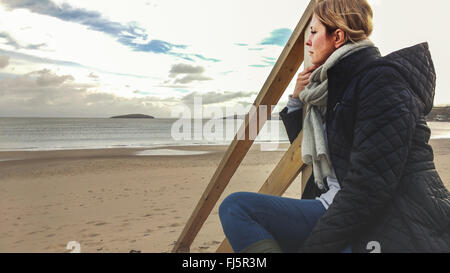 young woman sitting on wooden stairs on the beach - Stock Photo