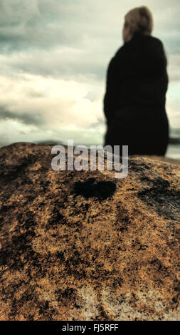 woman standing on beach by the rock - Stock Photo