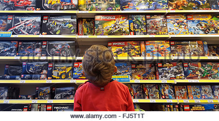 little boy admiring a plaything-shelf with LEGO packings - Stock Photo