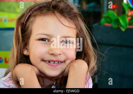 girl in good mood resting head on hands, portrait of a child, Germany - Stock Photo
