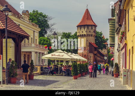 SIBIU, ROMANIA - 06 MAY, 2015: Unidentified people wander along the medieval defense wall and The Carpenters' Tower - Stock Photo