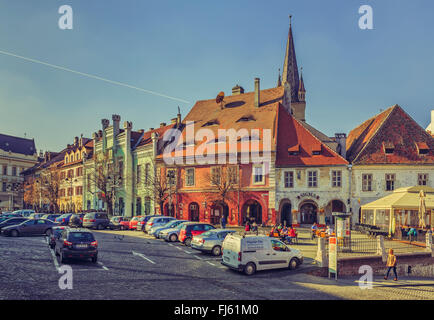 SIBIU, ROMANIA - 13 NOVEMBER, 2015: The Small Square with parking lot, the second fortified square in the medieval - Stock Photo